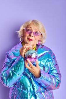 Aufgeregte ältere frau feiern die party, trinken getränk allein posiert an der kamera isoliert über lila raum