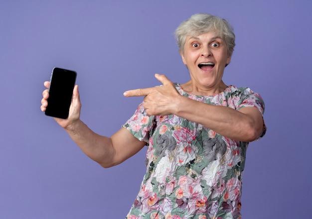Aufgeregte ältere frau hält und zeigt auf telefon lokalisiert auf lila wand