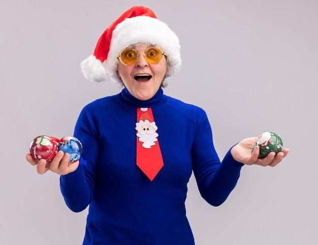 Aufgeregte ältere frau in sonnenbrille mit weihnachtsmütze und weihnachtskrawatte, die glaskugelverzierungen lokalisiert auf weißem hintergrund mit kopienraum hält