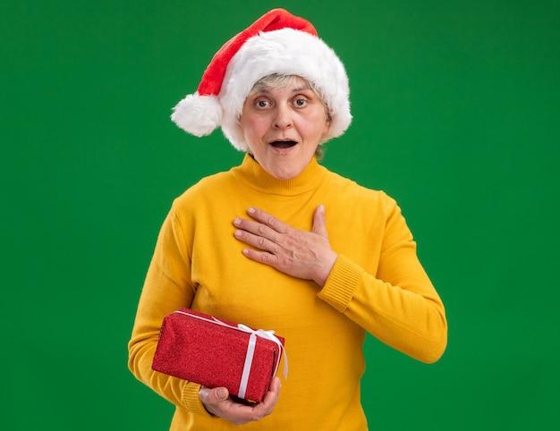 Aufgeregte ältere frau mit weihnachtsmütze legt hand auf brust und hält weihnachtsgeschenkbox lokalisiert auf lila hintergrund mit kopienraum