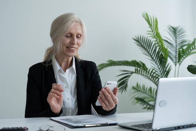 Aufgeregte ältere geschäftsfrau genießt die guten nachrichten auf ihrem handy, während sie an ihrem schreibtisch im büro sitzt