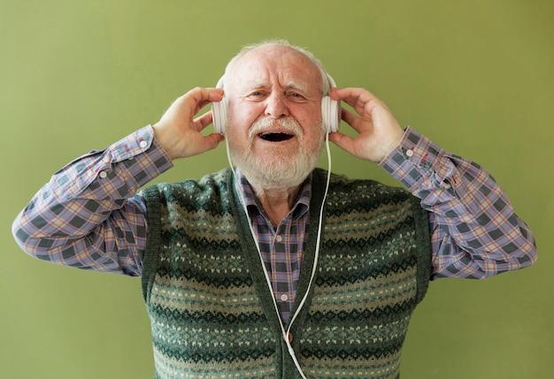 Aufgeregte ältere hörende musik der vorderansicht