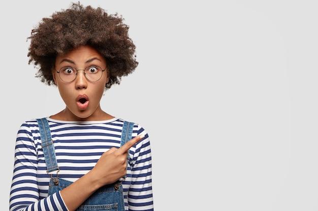 Aufgeregte ängstliche schöne junge afrikanische frau mit lockigen schwarzen haaren
