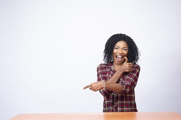 Aufgeregte afrikanische dame deutet auf den raum auf ihrer seite und zeigt einen daumen nach oben