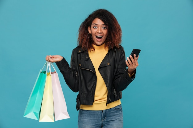 Aufgeregte afrikanische frau, die einkaufstaschen und handy hält.