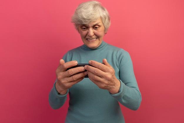 Aufgeregte alte frau mit blauem rollkragenpullover, die ein spiel am telefon spielt, isoliert auf rosa wand