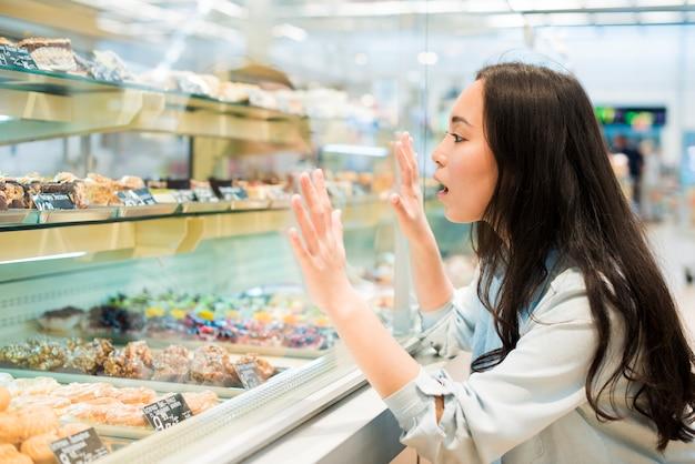 Aufgeregte asiatische frau, die auf süßigkeiten in der konditorei schaut
