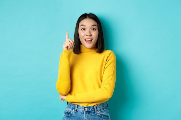 Aufgeregte asiatische frau mit kurzen dunklen haaren, die eine idee aufwirft, den finger in der heureka-geste hebt und lächelt, auf blauem hintergrund stehend
