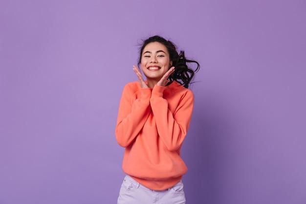 Aufgeregte asiatische frau mit pferdeschwanz, der zur kamera lacht. studioaufnahme der glücklichen chinesischen frau, die positive gefühle ausdrückt.