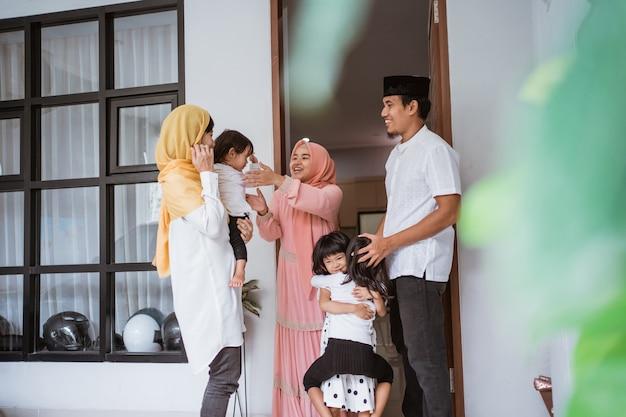 Aufgeregte asiatische muslimische familie, die freund während eid fitri mubarak zu hause besucht