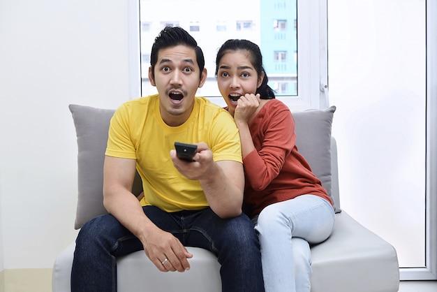 Aufgeregte asiatische paare, die auf der couch sitzen und filme aufpassen