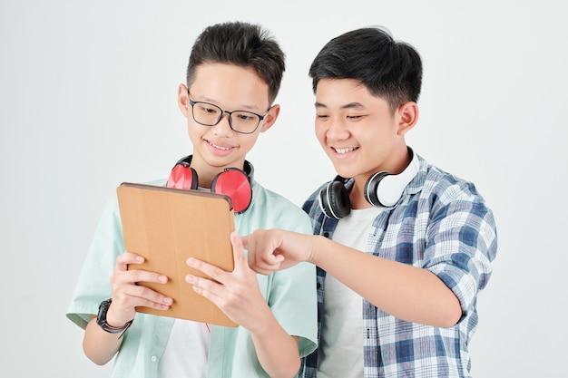 Aufgeregte asiatische teenager diskutieren neue anwendung auf tablet-computer