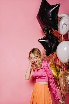 Aufgeregte blonde frau bereitet sich auf party vor