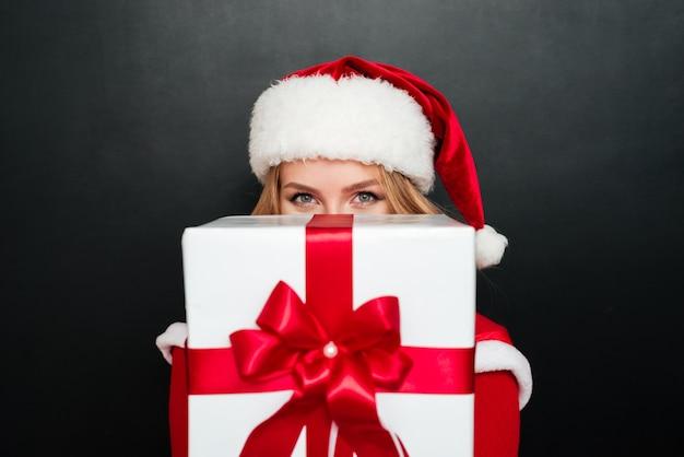 Aufgeregte blonde frau im roten weihnachtsmann-kleid, die große geschenkbox nach vorne isoliert auf der schwarzen oberfläche gibt