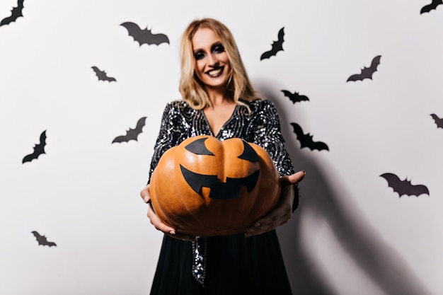 Aufgeregte blonde frau mit schwarzem make-up, das halloween-kürbis hält. lächelndes weibliches modell im hexenkostüm, das auf vampirparty aufwirft.