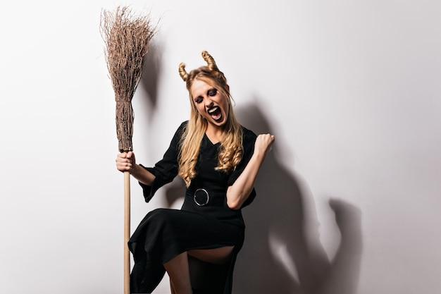 Aufgeregte blonde hexe, die mit besen aufwirft. schöner vampir im schwarzen kleid, das glück in halloween ausdrückt.