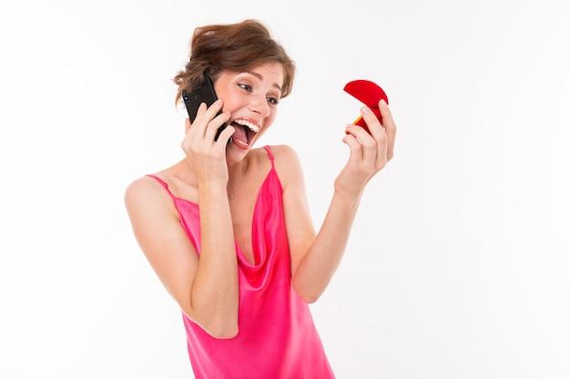 Aufgeregte braut mit einem ehering in ihren händen sprechend am telefon