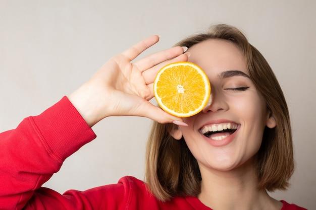 Aufgeregte brünette frau, die mit einer halben orange posiert und ein auge bedeckt, gegen weiße wand. platz für text