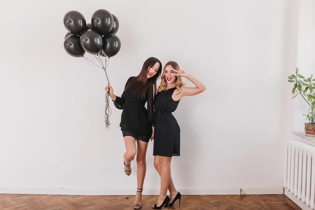 Aufgeregte brünette frauen in stilvollen schuhen mit hohen absätzen, die auf einem bein stehen und luftballons halten