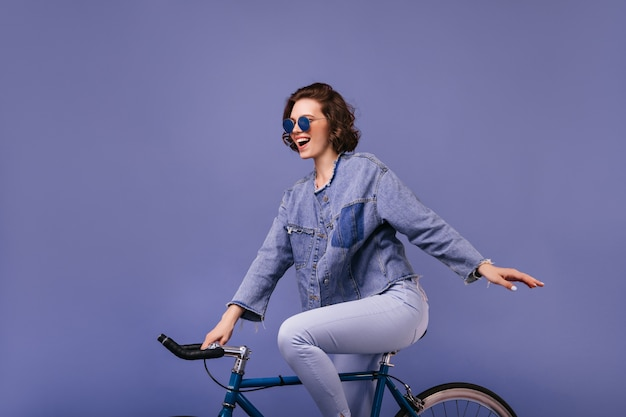 Aufgeregte charmante frau, die auf fahrrad aufwirft. innenfoto der atemberaubenden radfahrerin isoliert.