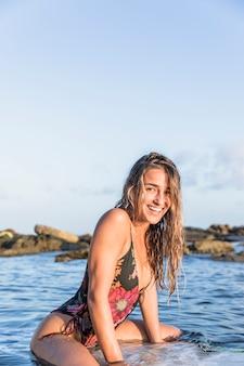 Aufgeregte dame, die auf surfbrett sitzt