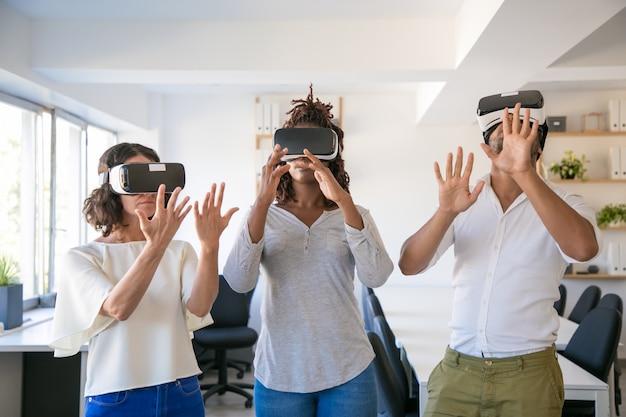 Aufgeregte dreiköpfige mannschaft, die virtuelles spiel spielt