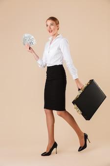 Aufgeregte emotionale junge geschäftsfrau, die koffer mit geld hält.