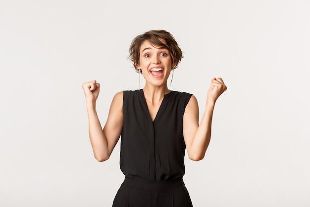 Aufgeregte erfolgreiche junge frau, die sich glücklich fühlt, optimistisch lächelt und faustpumpe, sieg über weiß feiert.