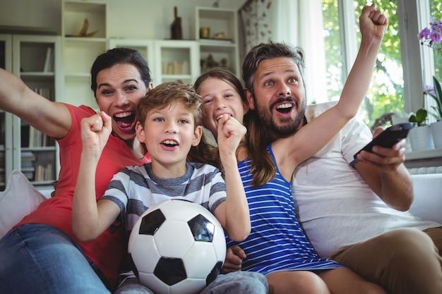 Aufgeregte familie, die fußballspiel beobachtet