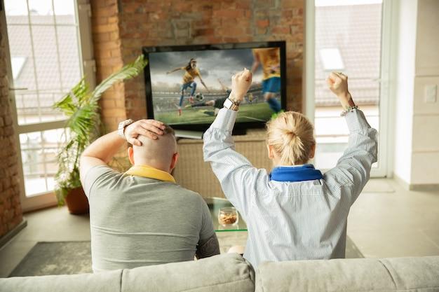 Aufgeregte familie, die weibliche fußballmeisterschaft, sportmatch zu hause beobachtet. schönes kaukasisches paar, das für die nationalmannschaft mit übersetzung zujubelt. konzept der menschlichen emotionen, unterstützung, spaß.