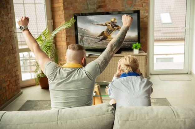 Aufgeregte familie, die zu hause ein american-football-meisterschaftsspiel sieht