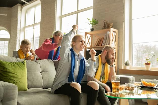 Aufgeregte familie, die zu hause ein fußballspiel guckt großeltern, eltern und kind