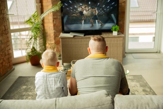 Aufgeregte familie, die zu hause ein kampfsport-meisterschaftsspiel beobachtet vater und sohn