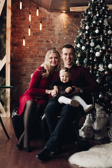 Aufgeregte familie mit entzückendem baby am weihnachten