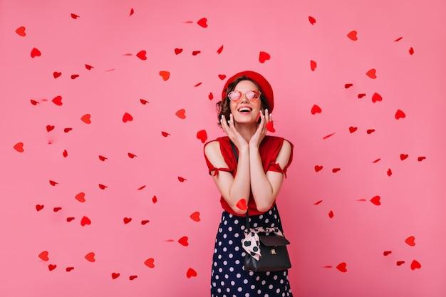 Aufgeregte französische weiße frau, die konfetti mit aufrichtigem lächeln betrachtet. ansprechendes kurzhaariges mädchen, das valentinstagsparty genießt.