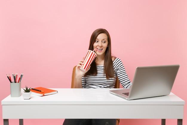 Aufgeregte frau, die aus einer plastiktasse mit cola-soda trinkt, sitzt am projekt im büro am weißen schreibtisch mit zeitgenössischem pc-laptop einzeln auf rosafarbenem hintergrund. erfolg geschäftskarriere. platz kopieren.