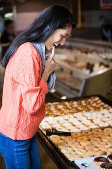 Aufgeregte frau, die donuts auswählt