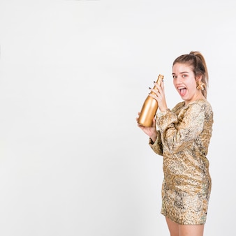 Aufgeregte frau, die flasche champagner zeigt