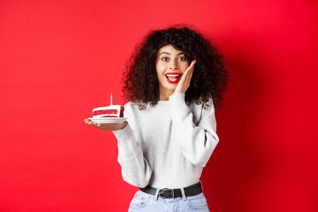 Aufgeregte frau, die geburtstag feiert, kuchen hält und überrascht und glücklich an der kamera, roter hintergrund schaut.