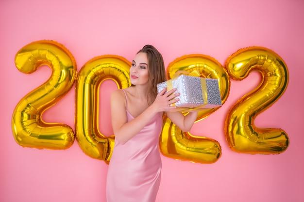 Aufgeregte frau, die geschenkbox einzeln auf rosafarbenem hintergrund rüttelt, goldene luftballons neues jahr