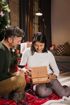 Aufgeregte frau, die ihr geschenk öffnet