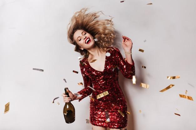 Aufgeregte frau, die ihre haare beim tanzen auf der party winkt