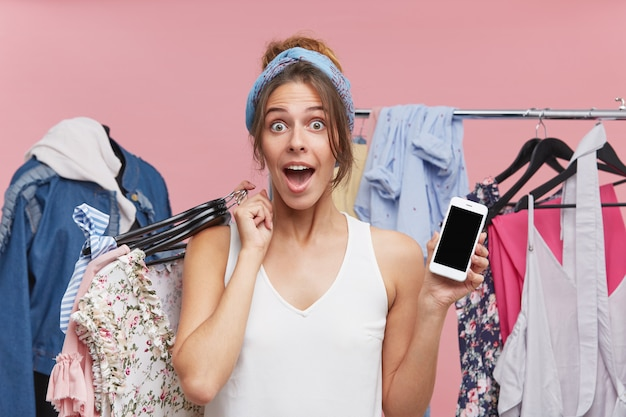 Aufgeregte frau, die mit großer überraschung schaut, kleiderbügel mit kleidern hält, während sie in der garderobe steht und handy mit leerem bildschirm demonstriert. menschen, einkaufen, technologiekonzept