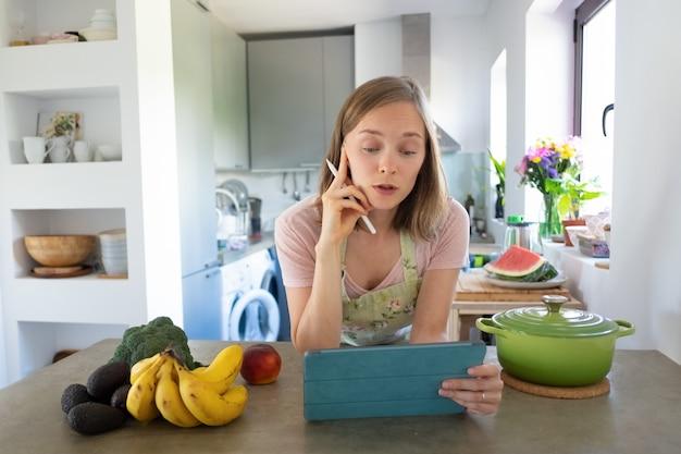 Aufgeregte frau, die online-kochkurs in ihrer küche beobachtet, sich auf tisch lehnt, tablette in der nähe von topf und frischem obst auf theke verwendet. vorderansicht. kochen zu hause und gesundes essen konzept