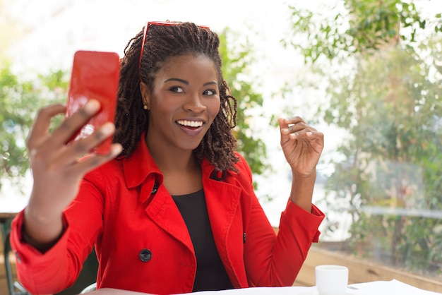Aufgeregte frau, die selfie im café nimmt