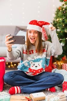 Aufgeregte frau, die selfie mit weihnachtshut nimmt