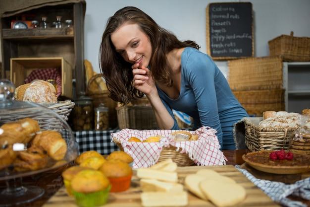 Aufgeregte frau, die süßes essen am bäckertisch kauft