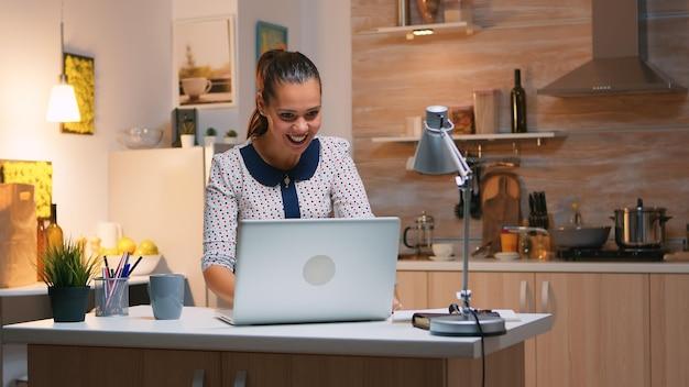 Aufgeregte frau fühlt sich ekstatisch beim lesen großartiger online-nachrichten auf dem laptop, der von der heimischen küche aus arbeitet. glücklicher mitarbeiter, der moderne drahtlose technologie verwendet, überstunden beim schreiben und suchen macht