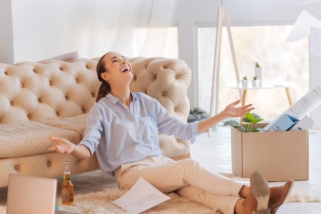 Aufgeregte frau. glückliche junge fröhliche frau, die auf dem boden sitzt, ihren kopf zurücklehnt und lächelt, während sie erfreut ist, einen neuen wunderbaren job zu bekommen