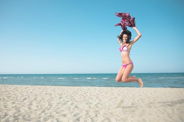 Aufgeregte frau im badeanzug, der auf den strand springt